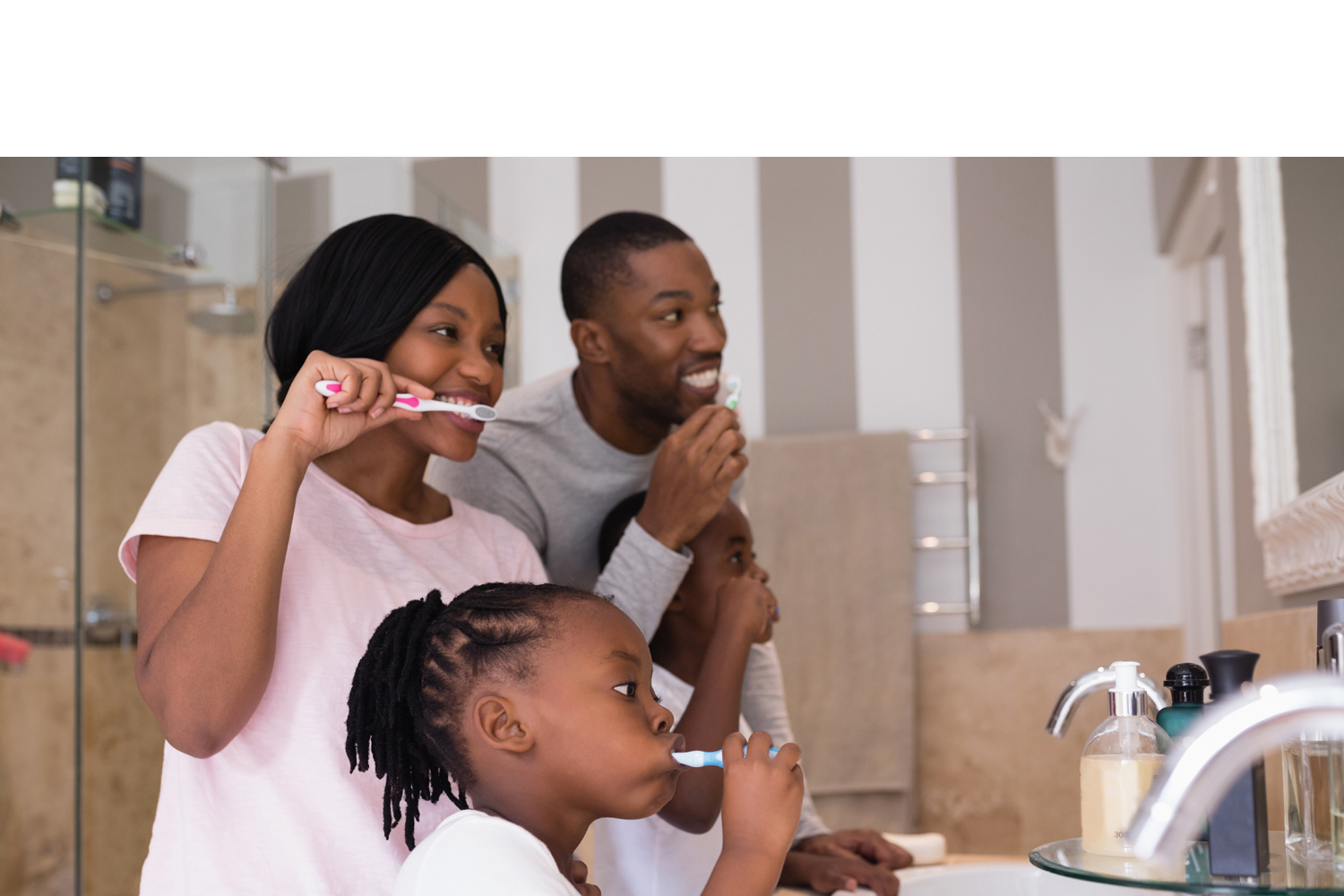 Parents with children brushing teeth in bathroom at home
