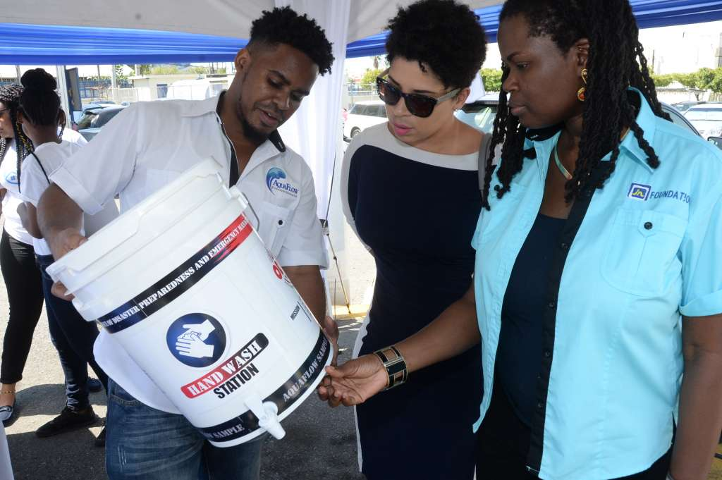 Onyka Barrett Scott (right), general manager for JN Foundation and Anaitee Mills, consultant, Climate Change Sustainable Division at the Inter-American Development Bank examine a converted keg being shown by Jovan Evans of Aquaflow Products and Services at the Water Tech-Fest.