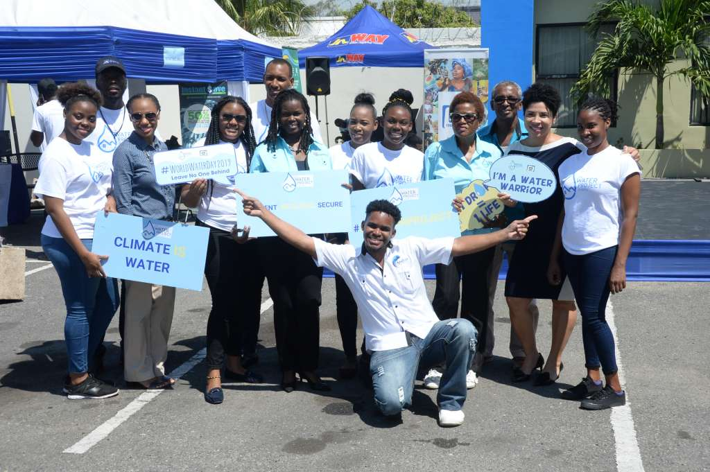 Onyka Barrett Scott (fourth from left), general manager for JN Foundation leads the charge of water conservation messages along with volunteers and partner, Anaitee Mills (second from right standing), Consultant, Climate Change Sustainable Division at the Inter-American Development Bank. Occasion was Water Tech-Fest exhibition that was mounted at the JN Bank Half-Way-Tree Branch by the Water Project Jamaica in observation of World Water Day on Friday, March 22.